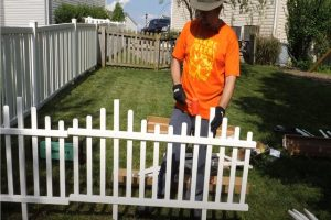 Glendale Fence employee installing vinyl picket fence