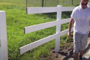 Glendale Fence worker installing vinyl rail fence