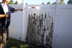 Glendale Fence Intsallation worker cleaning the white pvc fence